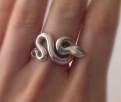 Minimalist Snake ring in solid sterling silver. Snake Snake rests snugly on your finger and its little head head juts out a bit onto the adjoining finger, but doesnt get in the way when wearing. I carved this little guy in wax first and then had him cast. Entirely hand finished and