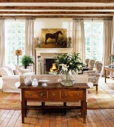 Rustic wood floors, wood ceiling beams, English pine furniture and a horse painting lend an air of elevated European country style to this light-filled living room.