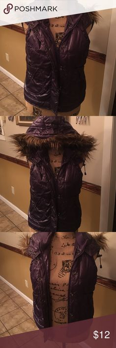 Hooded puffer vest Vest is purple with brown fur on the hood. Vest has pockets snap fasteners and also have two zippers one to zip up and the other one to zip down.  Fur is detachable from hood. Vest is 100% polyester. Vest does have lining. Fur is not real animal fur. Vest has been worn a few times in great condition. Vest is a size large Jackets & Coats Vests