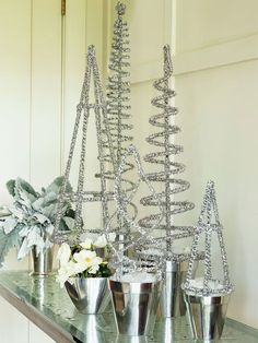 Glittery Tinsel Topiaries.  Put a sparkling holiday spin on basic wire topiary forms, found at garden supply and florist shops. Tightly wrap fine-gauge tinsel garland around each form and secure. Wedge a block of polystyrene foam into a silver-tone flowerpot and insert topiary.
