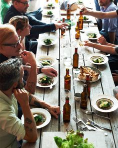 Diners at the rough-hewn table sit down to a casual, family-style meal of stew, bread, onions, and greens