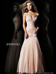 Feel the romance of this Sherri Hill prom dress 21069 when you wear it to your social event. This stunning design features a fit and flare silhouette perfect to flatter your body shape. The bodice has a pronounced sweetheart neckline with feminine cap sleeves, both accented by exquisite beading and embroidery. Subtle ruching runs from top to the dropped waistline which is also enhanced with beaded floral details. The full-length skirt is made of Tulle material for added elegance…