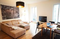Schöne Wohnzimmer-Einrichtungsidee: Warme Farben für Couch und Boden, große Fenster und großes Kunstdruck an der Wand.  WG-Zimmer in Berlin Mitte. #livingroom