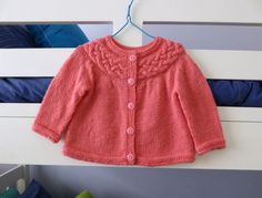 A gorgeous style of cardigan for a baby girl, in a watermelon / coral pink colour. (Its hard to describe the colour... pinkish but with a peachy