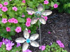 """Latest experiment for yard art.  Spoon flowers and small bowls as flowers. For spoon flowers, used cheap spoons and bent the handles off.  Used J & B weld glue and two washers and made a """"sandwich"""" with spoons in middle.  Attached elbow fitting to back and put in pole.  Super fun!!!"""