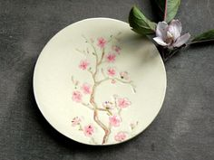 I made a small round ceramic dish from white clay and created a Cherry Blossom motif on it, with lots of romantic details. I painted with pink, brown,