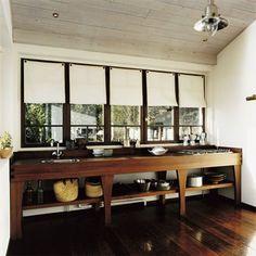 La cuisine est installée dans un cabanon en pin,  elle est équipée d'un long meuble en ipé placé devant une rangée de fenêtres.