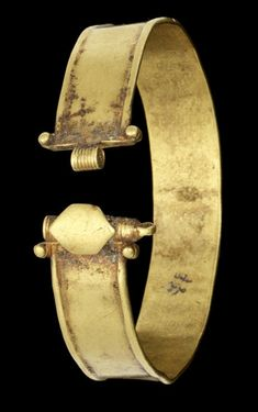 A Roman gold bracelet   Circa 1st-3rd Century A.D.  The hoop composed of a strip with raised borders, terminating in a spiralled clasp with applied granules and an applied sheet gold hexagonal plaque, the pin now missing, 2¼in (5.5cm) diam