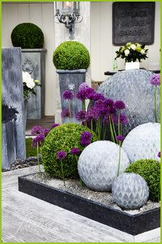 RHS Chelsea Flower Show |  'A Place in the Garden' looked so inviting with the round balls of flowing water, boxwoods added for a touch of green and striking purple allium continuing the circular theme throughout.  To read more: http://floatingpetals.net/the-rhs-chelsea-flower-show-part-1/