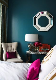 Deep #teal #bedroom wall #color with pops of fuchsia. Loving the octagonal #mirror and console as well!