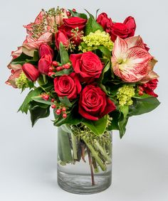 Peppermint Charm This beautiful collection of red roses, tulips, and variegated amaryllis is accented with simple greens and berries and designed in our signature glass cylinder vase.