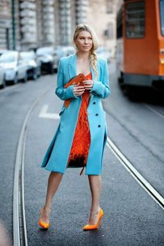 Light sky blue long stylish coat with portland orange mini dress and yellow orange mix cute high heels pumps and brown leather clutch
