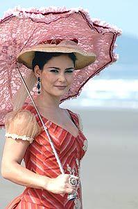 Carla Regina exibe mais uma sombrinha que é um dos destaques do figurino da novela Essas Mulheres  Foto: Record/Divulgação