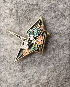 Flowery origami crane enamel pin. I've grown fond of putting pins on the upper breast of button downs.