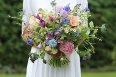 Natural and wild garden style hand tied bridal bouquet. Mixture of British flowers and foliage in peach, blues, pinks, lilacs and greens