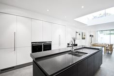 Black and white kitchen with kitchen island in a modern home extension. Matt white handleless kitchen units are combined with a dark Terra Oak kitchen finish for the room's central island.