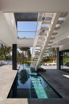 Lagula Arquitectes designed La Vinya, a residence whose top floor cantilevers over an open air space partially covering an L-shaped pool.