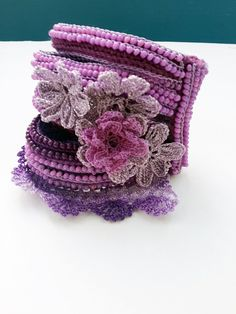 This unique beaded bracelet cuff is crochet from 100% cotton thread with resistant colors. For making it I used Free Form Crochet Techniques and I cant reproduce it the same again. The edging of the bracelet is crochet in purple and beige colors and it is decorated with sun stone beads in ink color. The colors of the base are ink, purple, lilac, pink and beige and it is decorated with beaded crochet flowers. For the inner part of the flowers I used natural fluorite and agate beads in purple…