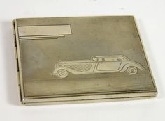 An Art Deco Motoring Cigarette Case, - silver-tone cover with blank cartouche and engraved 1930s era coupe, spring loaded hinged lid.