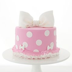 Pretty pink polka dot cake for a sweet little 2 year olds Birthday. With it's bow and little ruffles this tied in beautifully with her Minnie Mouse themed Birthday Party.