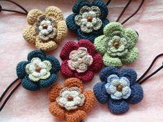 「ぷっくり彩り花ゴムⅡ(秋バージョン)」秋を意識した色で仕上げてみました。 3段目の花びらを大きくして色を強調してみました。[材料]毛糸(各色)/ビーズ(約5~6mm程度)/ゴム