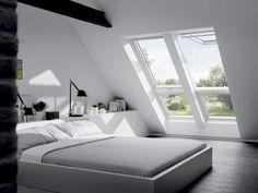 Chambre aménagée dans un grenier et éclairée par des fenêtres de toit Velux