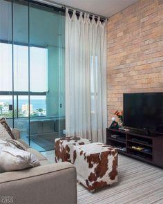 """A sala de TV deste apartamento não passa despercebida graças aos pufes de pele de vaca, úteis como mesa de centro ou apoio para os pés, e à parede de tijolos. """"Achei que combinou com os outros acabamentos naturais"""", explica a arquiteta Marcia Meccia."""