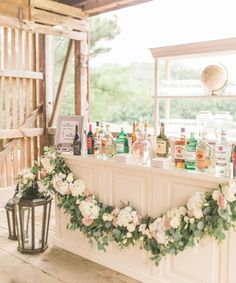 A rustic wedding . Natural backlighting, a blush floral garland, and decorative lanterns create a romantic vibe for this white wedding bar ? Wedding On A Budget, Wedding Reception Venues, Wedding Catering, Wedding Themes, Wedding Decorations, Wedding Ideas, Themed Weddings, Reception Ideas, Wedding Dresses