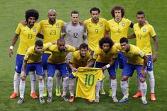 Brazil's Bernard, center, and Brazil's Marcelo hold the jersey of injured teammate Neymar as the team poses for photos before the World Cup semifinal soccer match between Brazil and Germany at the Mineirao Stadium in Belo Horizonte, Brazil, Tuesday, July 8, 2014