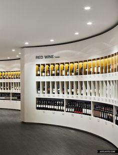 Retail Design | Wine Store | BWS | Liquor Store | Original manera de presentar los diferentes tipos de vinos, con tres nieveles perfectamente delimitados y una iluminación por cada espacio, es decir, para cada una de las botellas del establecimiento para destacar los mejores vinos por separados. A parte me gusta el diseño curvo de la góndola.
