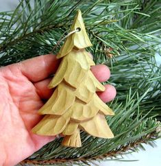 This interesting pine tree ornament was carved by me out of poplar wood. The board I used was white and green with a little bit of purple. I cut the tree out of the green part so this tree is the natural color of the wood. It was not painted or stained but it was sprayed with