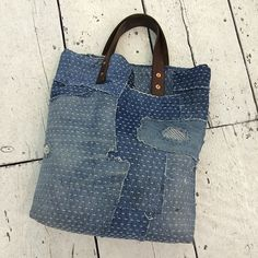 bag made from scraps of denim, with stitches, made by Darn and Dusted, who make…
