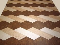 Cork Floor from Globus Cork: I wouldn't use this pattern, but it shows the way light and dark cork tiles could be used to tie the dark wood and light carpet floors together.