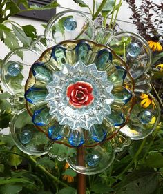 Garden flower suncatcher made from miscellaneous thrift store clear dishes. Ceramic rose accent for center.