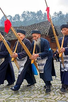 China, Guizhou province, Langde village, Long Skirt Miao people in traditional dress, mens are playing lusheng.