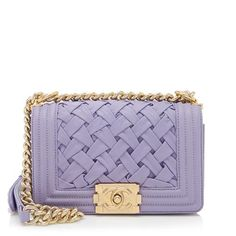 This rare Chanel Boy Bag is a limited edition piece from the Versailles Cruise 2013 Collection. It is made from woven lavender lambskin with antique gold-tone hardware. Details include a modern CC push lock and chunky chain and leather strap. The interior is lined in a beige textile with one open pocket. Carry this style with the strap doubled-over or pulled through.