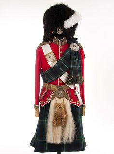 A BRITISH (SCOTTISH) UNIFORM OF A LIEUTENANT OF THE GORDON HIGHLANDERS, first quarter of the 20th century.  This very complete group include an black feather bonnet  with diced band, silvered badge and white feather plume.    Doublet of red wool with buff collar and cuffs, piped white, with gold bullion braid and regimental collar insignia, and with gold cord shoulder boards with rank insignia.  Wool kilt is in regimental tartan.