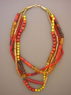 """A show-stopper. Amber-colored """"cornerless"""" beads from 1800s Bohemia, old and antique vulcanite heishi from Africa, long antique brass cylinders from the Yoruba tribe of Nigeria, and a scattering of other old beads come together to create this fun-filled necklace. Brass heishi, brass cones, and a gold-filled hook and eye clasp."""