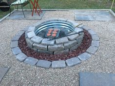 Backyard 12x12 firepit area off of the patio. All done on top of the ground and the only digging was an inch deep to seat the galvanized firepit ring. Filled in with drainage gravel and sand inside the ring. Additional pavers inside support the removable cooking grill. The rest is weed cloth , pavers, lava rock and pea gravel.