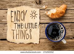 Inspirational early morning breakfast of a half eaten fresh croissant with filter coffee and a handwritten note - Enjoy the little things - reminding us to appreciate even the simple moments in life - stock photo