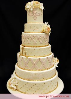 Each tier of this 7 tier wedding cake includes different detailed patterns including quilting, damask, dots and swirls.  White and pink orchids and lilies highlight the top tier.  Flavors include chocolate cake with raspberry chambord, chocolate and hazelnut fillings, vanilla cake with cannoli filling and chocolate buttercream, and pink velvet cake with chocolate mousse.