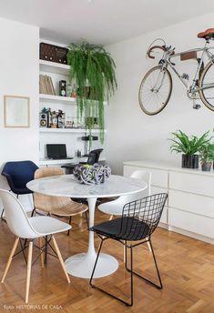 Sala de jantar com mesa tulipa redonda e suporte de bicicleta na parede tem cômoda branca como aparador e home office integrado.