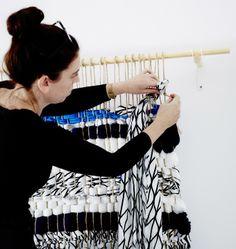 Designer de interiores pendura uma peça feita no tear à parede