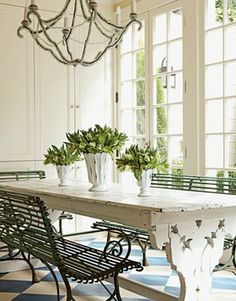 table next to french doors. big airy chandelier. greenery on table.