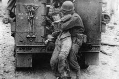 An American infantryman picks up a wounded German soldier on the road to St. Lo, France, and helps him into a half-track. The Nazi was abandoned by his own troops after being wounded. 20 June 1944.