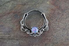 16 gauge (1.2mm) purple opal daith hoop ring, daith clicker, or septum hoop. A purple opal centered around a lacey hoop is made of 316L surgical steel set with the purple opal being 4mm. Can also be u