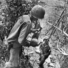 World War II: Innocence and Experience  In a Eugene Smith photo that somehow encompasses both tenderness and horror, a U.S. Marine cradles a near-dead infant pulled, literally, from under a rock while troops cleared Japanese fighters and civilians from caves on Saipan. No one seeing this image could doubt that the war in the Pacific -- and in Europe, and in North Africa -- was routinely subjecting troops to unimaginably nightmarish scenarios. The child pictured here was the only person found…
