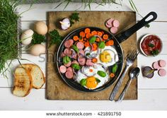 Fried eggs in a frying pan with vegetables , greens and crispy bread - stock photo