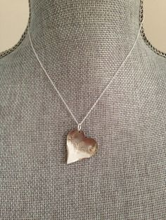 This necklace is made from the back of a vintage silver fork which was have cut down, filed into the shape of a heart and hung off a sterling silver chain. The result is this modern take on spoon jewelry.