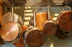 Closeup of hanging pots and pans in a kitchen Cafe Restaurant, Lifehacks, Copper Bottom Pans, Culinary Arts Schools, Copper Cooking Pan, Baking Gadgets, How To Clean Copper, Ideas Prácticas, First Kitchen